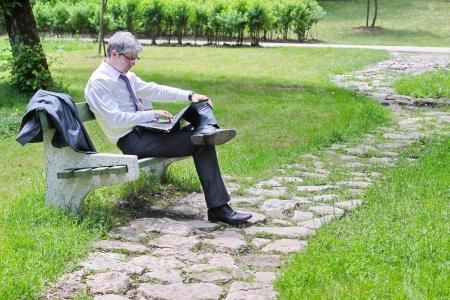 Businessman using laptop sitting on a bench