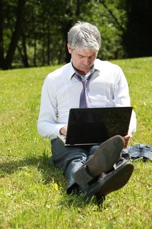 Businessman using laptop on a meadow Фото со стока