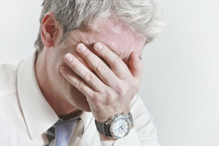 Businessman having head ache as a result of being under pressure    Фото со стока