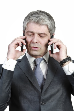 Businessman talking simultaneously on two cell phones    under pressure