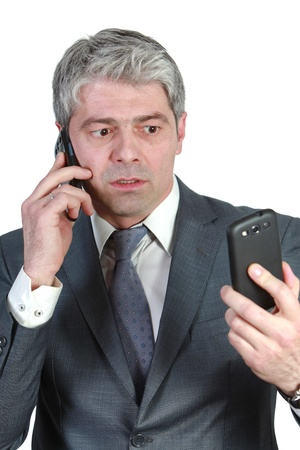 simultaneously: Businessman talking simultaneously on two cell phones    under pressure