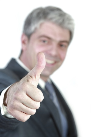 Successful young businessman showing thumb up