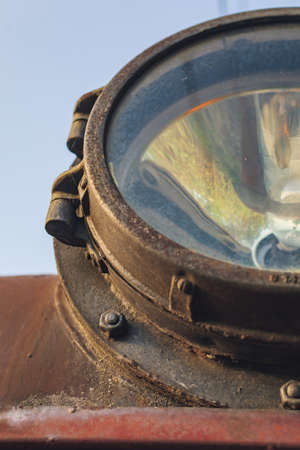 Fragment of old train headlight. Old rusty locomotive, close up.