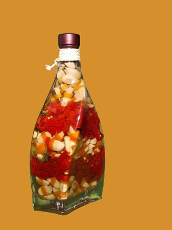 unusually: an unusually shaped bottle containing colourful chilli peppers and garlic cloves in vinegar Stock Photo