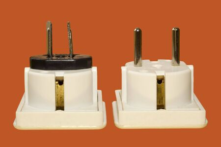 adaptable: a pair of travel adaptors on a bright orange background Stock Photo