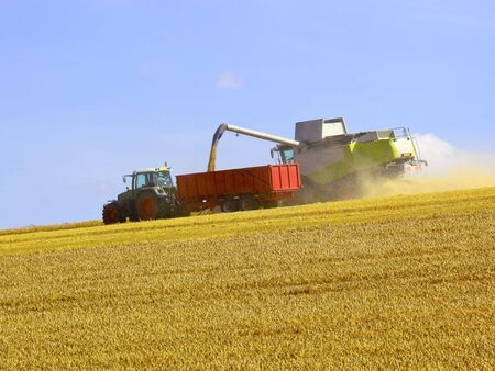 harvesting on the wolds in summer under a blue sky photo