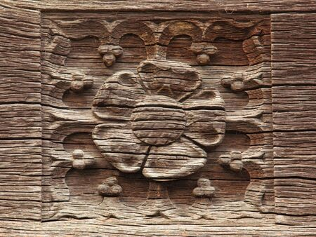 an old carving of a rose on wood photo