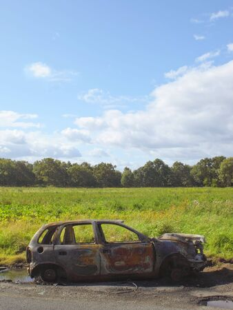 burnt out: a burnt out car by a roadside in summer Stock Photo