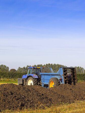 manure: a manure spreader in a field in summer