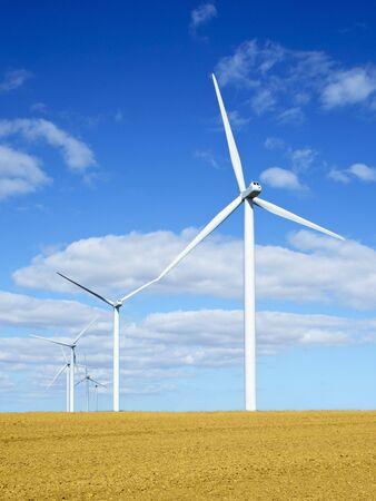 a line of wind turbines in a stubble field in summer photo