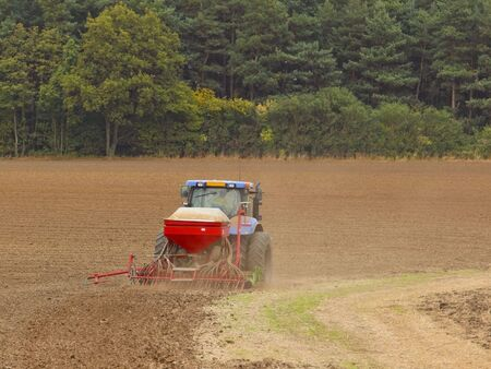 seed drill: tractor and seed drill in action on a dry september day Stock Photo