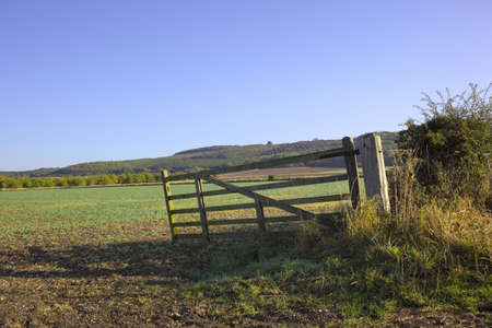 field gate with fields and tree covered hillsides in autumn photo