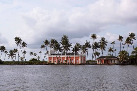 south india: a colorful church surrounded by palm trees by the banks of the backwaters of kerala south india