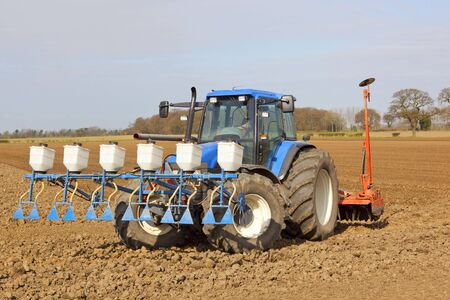 granular: a blue tractor applying granular pesticide and cultivating in springtime Stock Photo