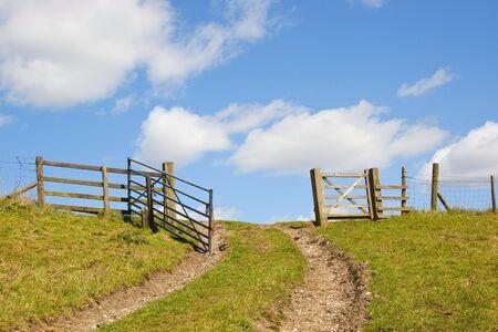 invitando: una puerta de enlace de invitar a sobre la parte superior de la ladera de una colina cubierta de hierba hacia el cielo azul con nubes esponjoso blancas