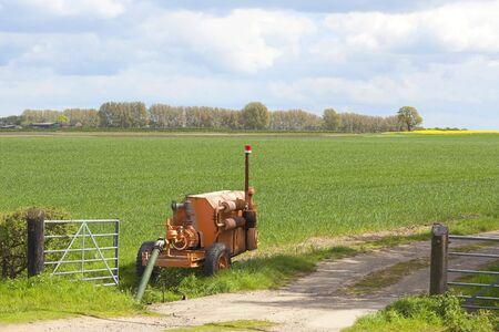bomba de agua: paisaje agr�cola con una bomba de agua de naranja para el riego de cultivos por una pista de granja con wheatfields y los �rboles en primavera