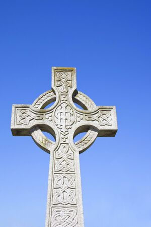 archtecture: an ancient cross decorated with celtic design against a blue sky