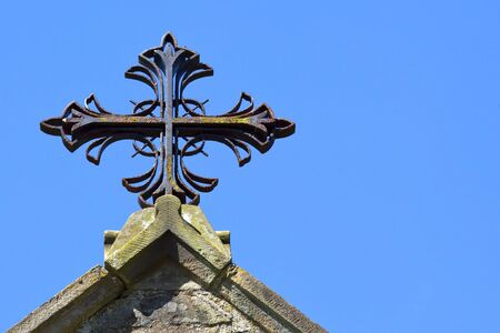 a close up of a metal decorative cross on a church roof under a bright blue sky in summer photo