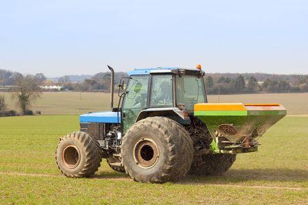 a tractor spreading fertilizer in springtime under a blue sky