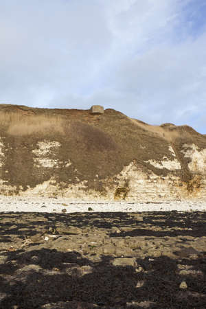 wartime: an english coastal landscape with eroded cliffs and wartime bunker under a blue sky