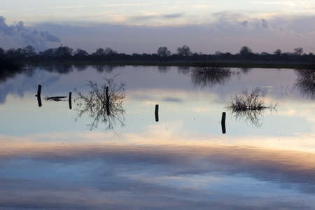 sky reflected in winter flood waters with fence posts in silhouette Stock Photo - 8660393