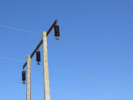 insulators: telegraph pole and power lines with brown ceramic insulators on blue sky