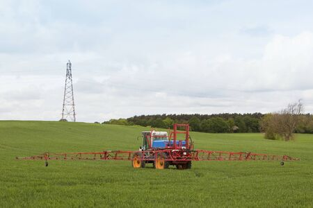 crop sprayer: agricultural crop sprayer in action under a cloudy sky Stock Photo