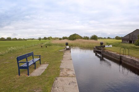 an english landscape with old traditional hand operated lock gates on a small canal with trees and hedgerows under a cloudy sky Stock Photo - 9574043