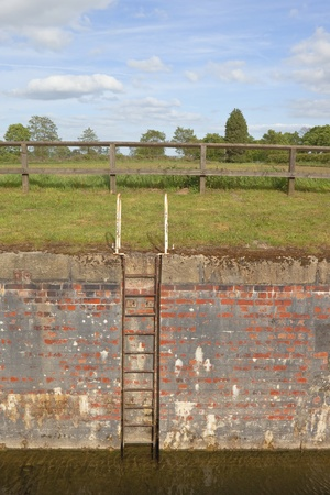 canal lock: an english landscape with a metal access ladder in a canal lock with fields and trees under a blue sky