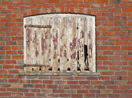 flaking:  background and texture of an old barn door with flaking paint and iron hinges set in a red brick wall Stock Photo