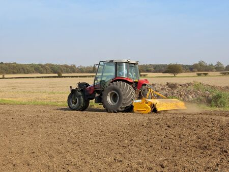 wheeled tractor: an unusual three wheeled tractor with yellow rotavator attached on a sunny autumn day