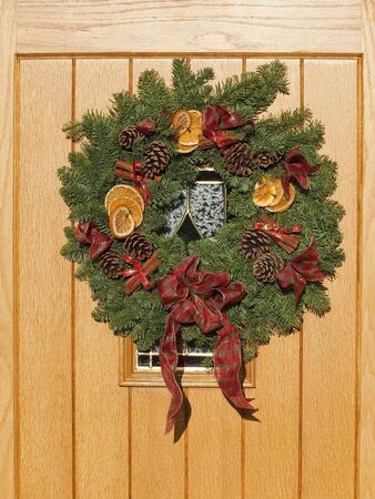 cinammon: a christmas wreath with pine cones orange cinammon sticks and ribbon on a new wooden door Stock Photo