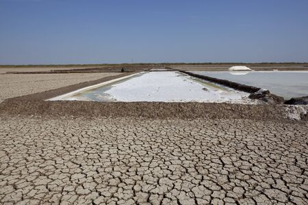 working salt pans on the little rann of kutch in gujarat india under a blue sky photo