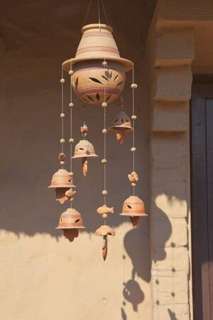 wind chime: a decorative ceramic wind chime with leaf design hanging from a sunlit doorway