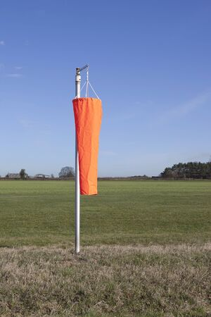 motionless: landscape with a bright orange wind sock on a rural grass airstrip hangs motionless on a calm day under a blue sky