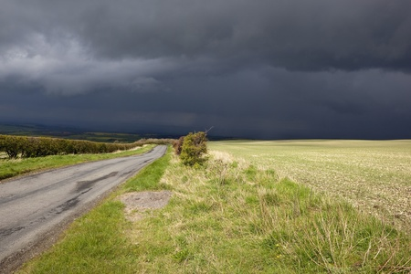 grass verge: a small rural road running through patchwork english fields with hegerows under a dramatic april sky
