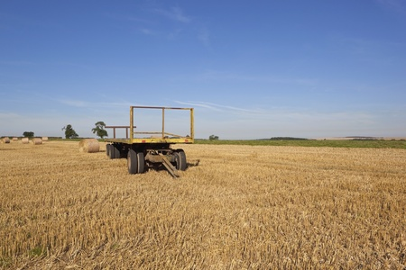 an agricultural landscape with a yellow trailer photo