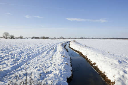 a freezing dyke in winter farmland with trees and hedgerows under a blue sky Stock Photo - 17604062