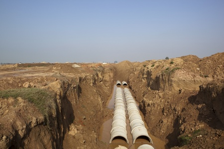 open trench: newly laid pipes in an open trench on a new construction site on the outskirts of Mohali Chandigarh Punjab India Stock Photo