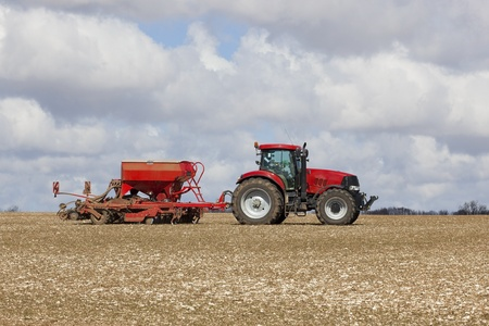 seed drill: a red tractor and seed drill on a chalky field in the yorkshire wolds england under a cloudy sky in springtime Stock Photo