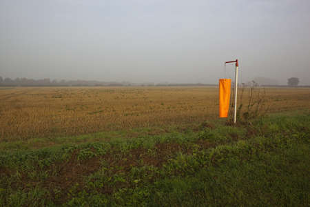 a bright orange wind sock beside a newly cut wheat field in autumn on a misty morning photo