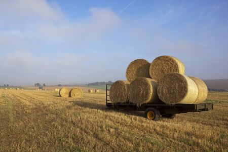 a farm trailer with a stack of round bales in a stubble field in the yorkshire wolds england in late summer under a blue sky photo