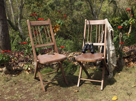 south india: two rustic wooden chairs with waistcoat and binoculars in a tropical garden in south india Stock Photo
