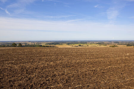 late summer: a plowed field with views of the vale of york under a blue sky in late summer Stock Photo