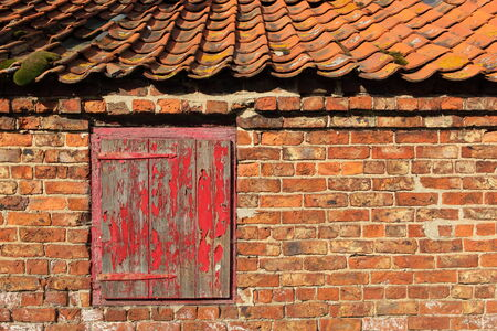 old red brick building with weathered wooden door and pantile roof photo