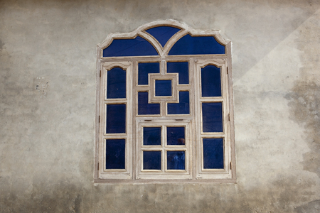 punjabi: a blue timber framed traditional punjabi window set in a rendered wall of a building in a Bishnoi village