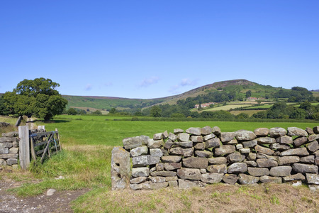 north gate: a dry stone wall with wooden gate in front of moorland scenery in the north york moors in summer under a blue sky
