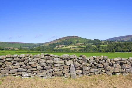 dry stone: a dry stone wall in front of rudland rigg on the north york moors under a blue sky in summer