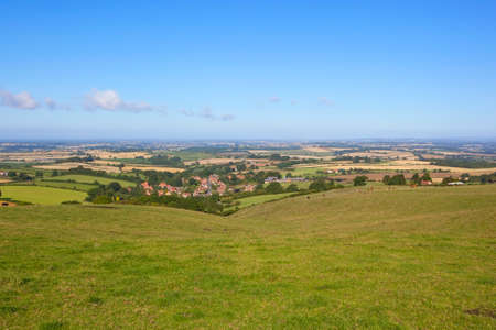 vale: a view of the vale of york from a hillside meadow on the yorkshire wolds england under a blue sky in summer