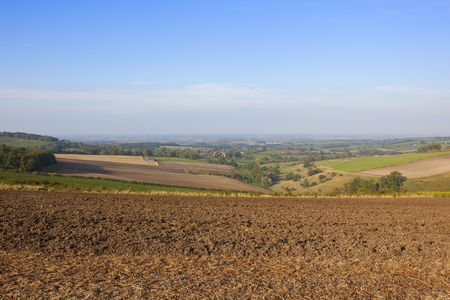 vale: a newly cultivated hillside field in the yorkshire wolds england with a view of the vale of york under a blue sky in autumn